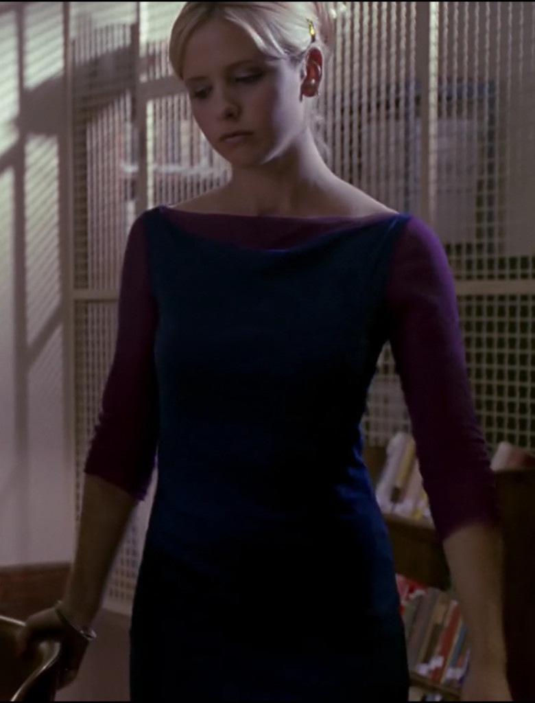 Buffy is wearing a navy blue, sleeveless boatneck dress over what appears to be a magenta t-shirt. Upon closer inspection, it's some kind of chiffon. But it still looks super weird and her modern beehive hairdo is not helping the cause.