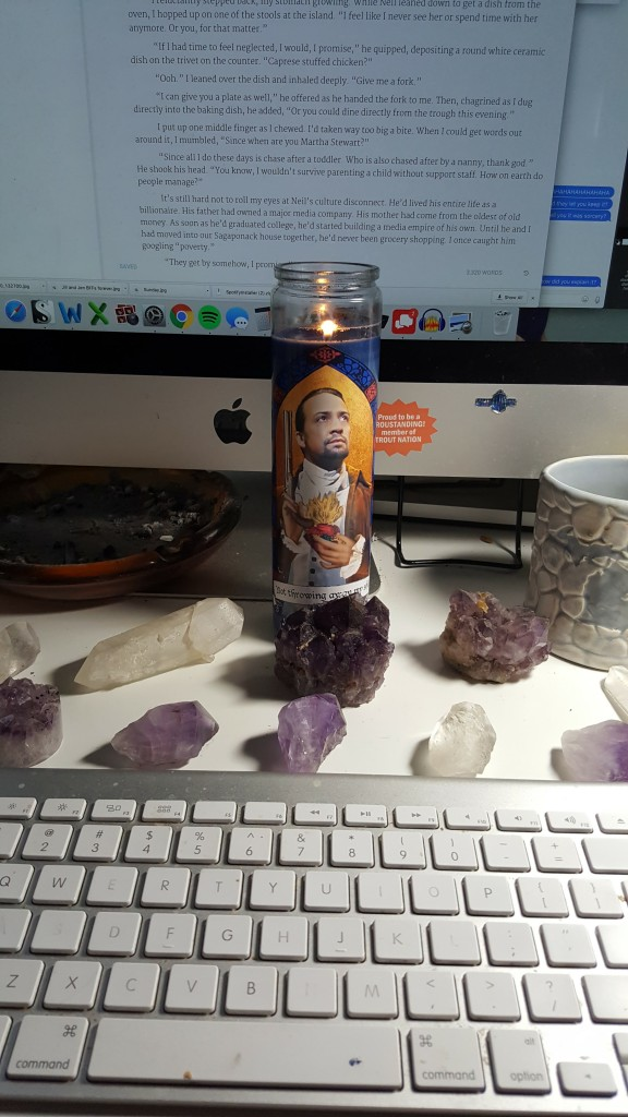 A prayer candle with Lin-Manuel Miranda dressed as Alexander Hamilton, surrounded by amethyst and quartz crystals of varying sizes, all arranged in front of my computer screen.