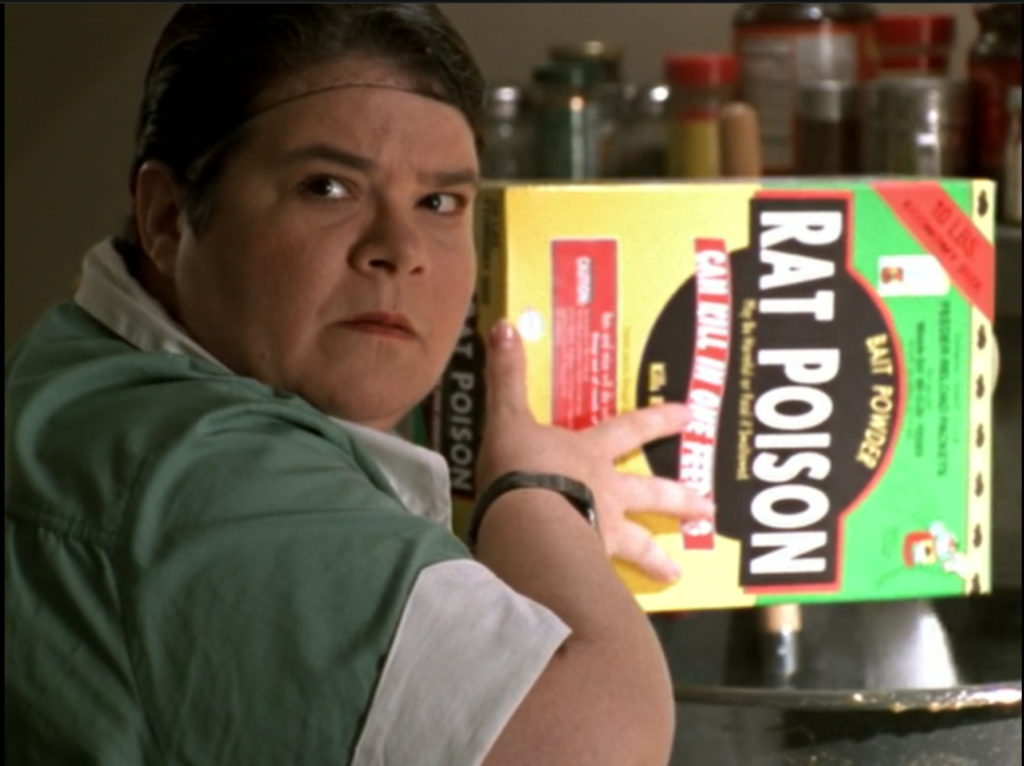 The lunch lady is pouring rat poison into the food.