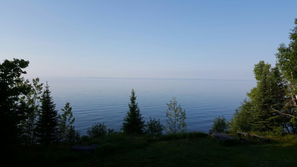 A stunning view of Lake Superior, framed by trees.