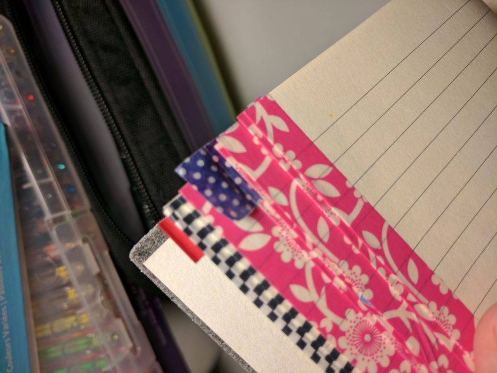 The corner of my notebook, with pages lined in contrasting washi tape and washi tape tabs.