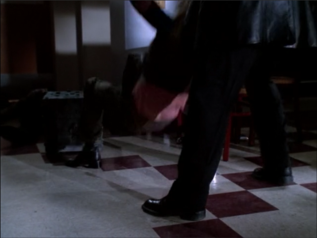 Angel is behind Buffy, lifting her off the floor with his hands under her armpits. There is a clear view of the floor with no evidence of a demon bug being there.