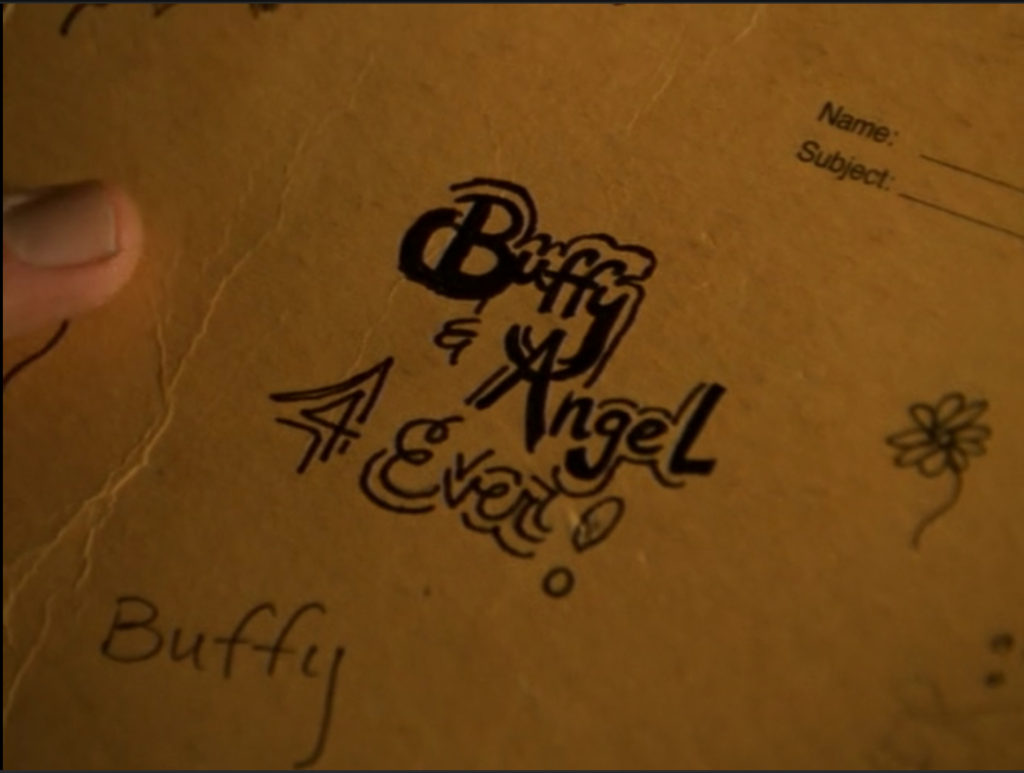"""Buffy has written """"Buffy & Angel 4 Ever"""" on her notebook, and the lettering is all fancy and underlined and carefully drawn out. Like, she took time on this."""