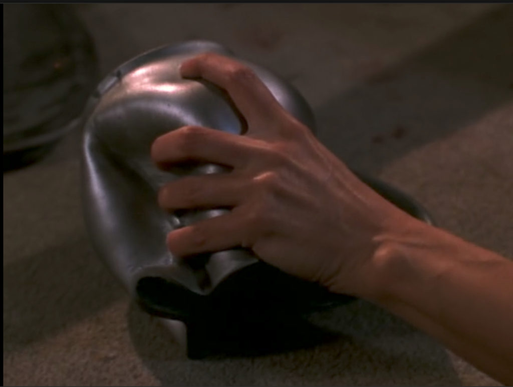Buffy's hand, squeezing dents into a metal pitcher
