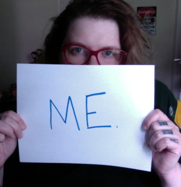 "Me, peering above a sign I am holding, which says, ""ME."""