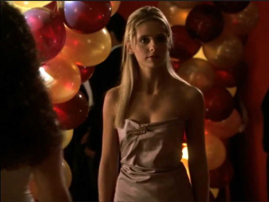 Buffy's dress is strapless, light mauve taffeta with a sort of gathered top with a jeweled broach or something at the top of the gathers. She did what she could with her hair, but honestly, she didn't have a lot of time on this one, with the Hell Hounds.