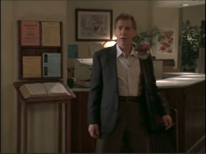 Mayor Wilkins standing in front of the library desk, shocked and offended with a sword jutting out of his chest.