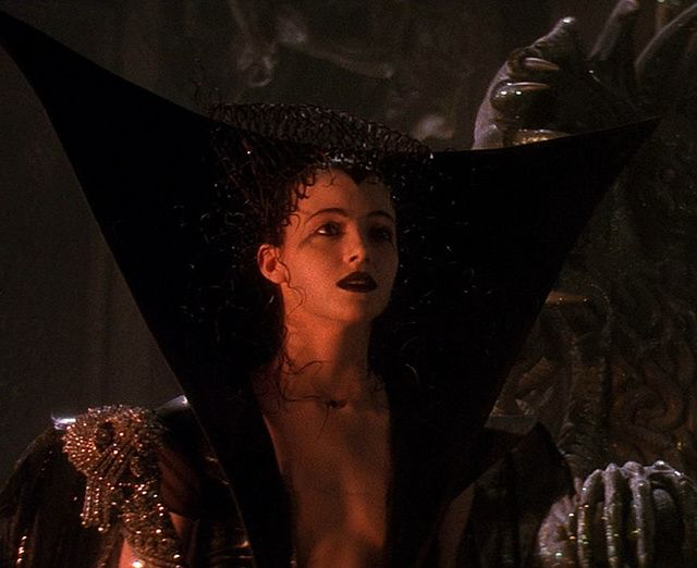 Mia Sara in Legend, wearing her Dark Lily costume. It's black, with a really tall collar that goes way up above her head like the back of a chair or something. The neckline is super low, and her makeup is all dark and dramatic.