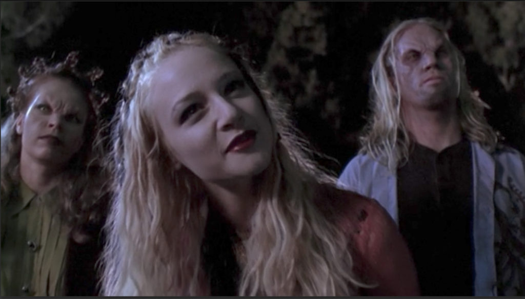 Three vampires. In the background, a red-headed one with her hair half-up in bantu knots and a goateed, surfer-haired dude. In the foreground, a girl with long blonde hair also half up in knots, but not the tall pointy one the other chick is sporting.