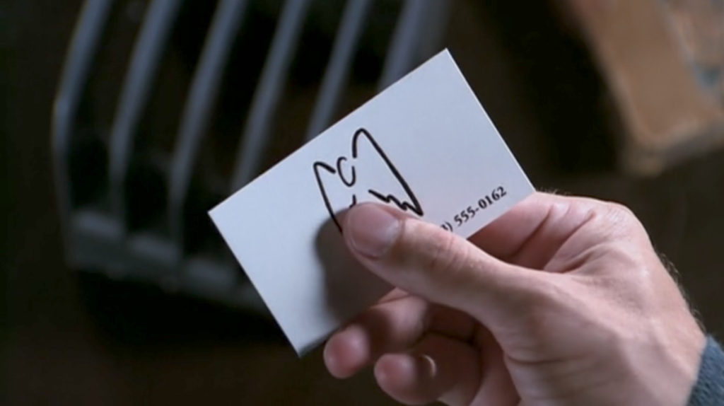 Angel holds a white business card with a stylized drawing that's basically a little oval with two wings.