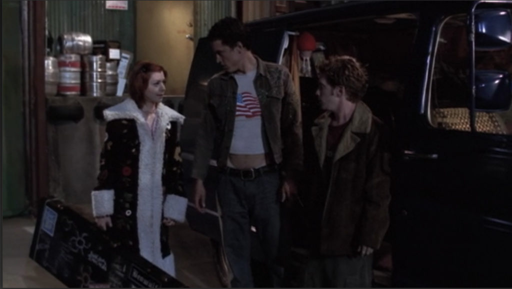 Willow, Devon, and Oz are standing next to Oz's van. Devon is wearing some kind of printed jacket over a t-shirt that's several sizes too small, revealing his abs and low-rise jeans.