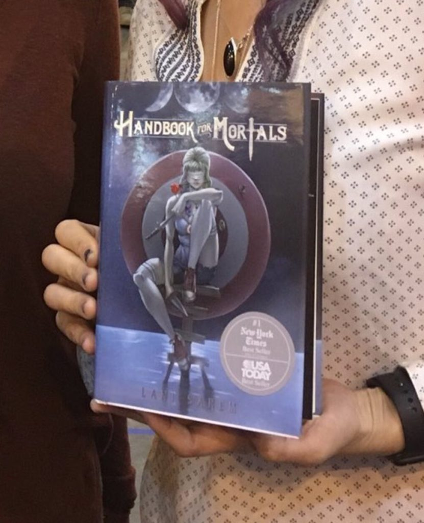 A photo of someone (possibly Sarem) holding a copy of Handbook For Mortals with a big gray sticker on it proudly declaring it a New York Times and USA Today bestseller. The sticker uses the logos of both newspapers.