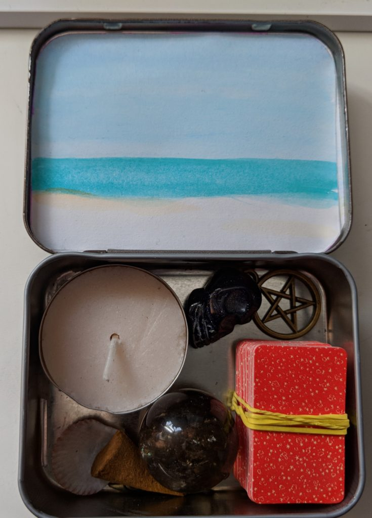 A photo of my purse-sized altar, a converted Sucrets tin with a tealight candle, a smoky quartz sphere, a small stone skull, a brass pentacle, a very, very tiny deck of tarot cards, a seashell, and a cone of incense. The inside of the lid of the tin has a water color scene of the ocean