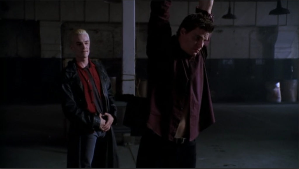 Angel is captured, suspended by his arms in the middle of a grim warehouse setting. Spike stands behind him, gloating.