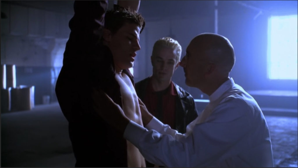 Angel is suspended by his arms and Marcus the torture guy has opened Angel's shirt while Spike looks on. Behind them is a gigantic window with sunlight streaming in.