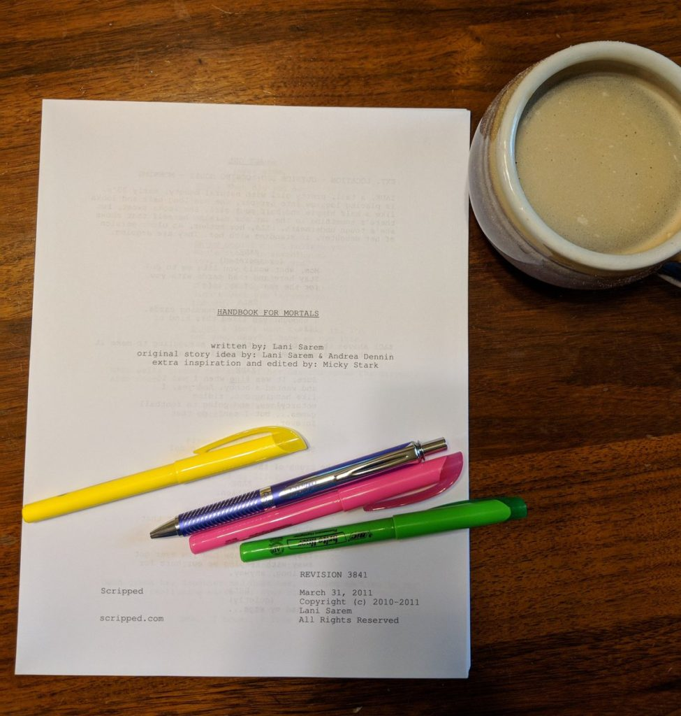 A photo of the Handbook For Mortals screenplay on my dining room table, with highlighters and a mug of coffee.
