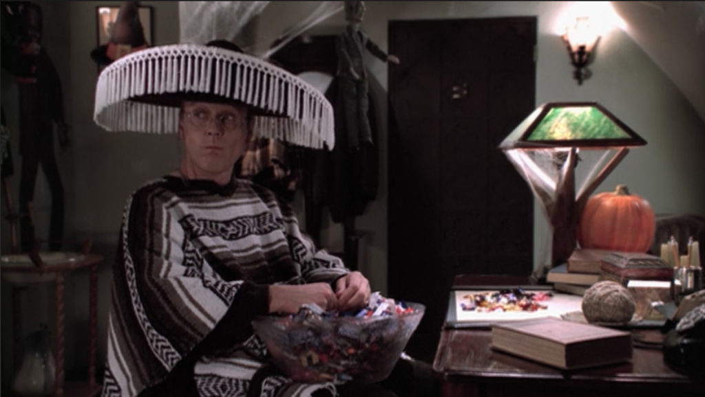 Giles is still in his stereotypical costume, sitting in his apartment at his desk with the trick-or-treat candy bowl in his lap, a mouth full of candy, and a pile of empty wrappers on the desk in front of him.