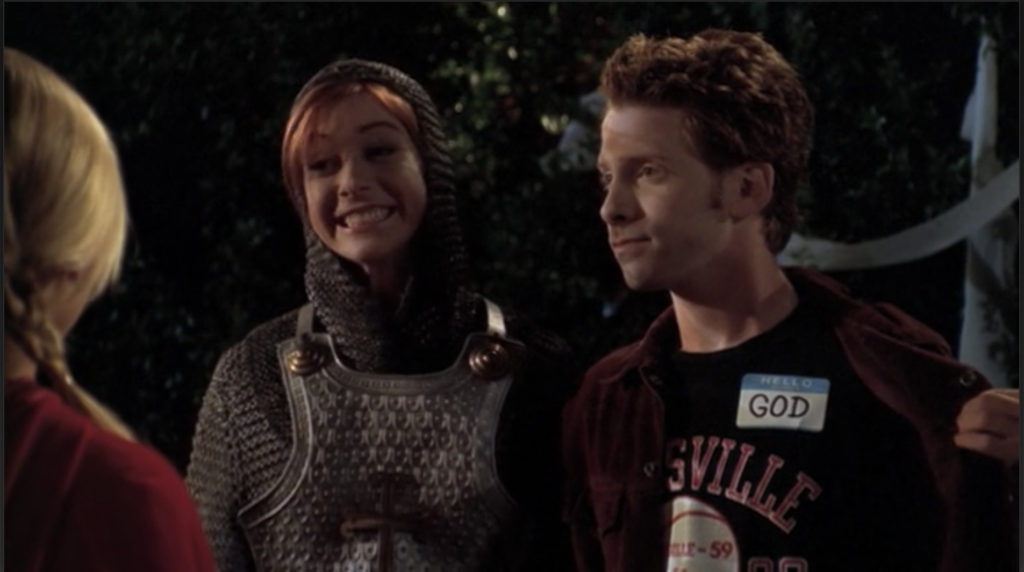 Oz pulling back his jacket to reveal a name tag that reads GOD, while Willow beams proudly at their joke.
