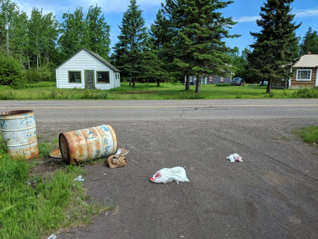 A driveway. Across the street are two small cabins. At the end of the driveway are two large oil barrels that have been repurposed as trash cans. The lids are off both and one is turned on its side. Garbage is strewn across the end of the driveway.