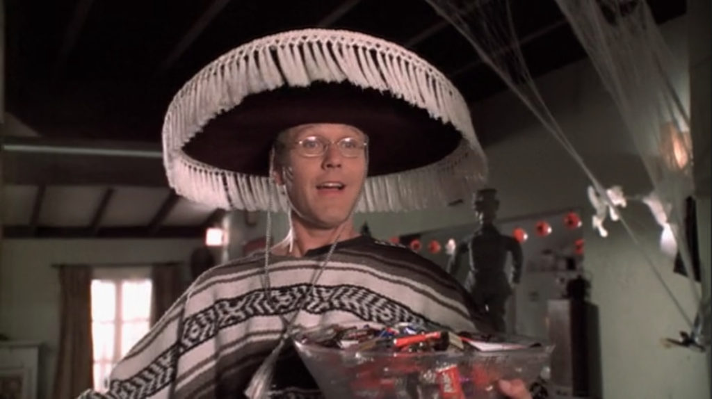 Giles is wearing a sarape and sombrero, holding a bowl of candy. He is uncharacteristically psyched for Halloween.