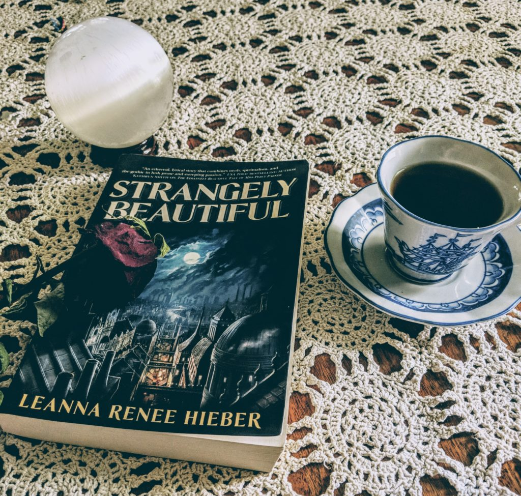A photo of the book Strangely Beautiful by Leanna Renee Hieber, staged on my crocheted white table cloth with a china cup of tea with saucer beside it, a dried rose resting across it, and a selenite crystal ball looking ghostly and beautiful above it.