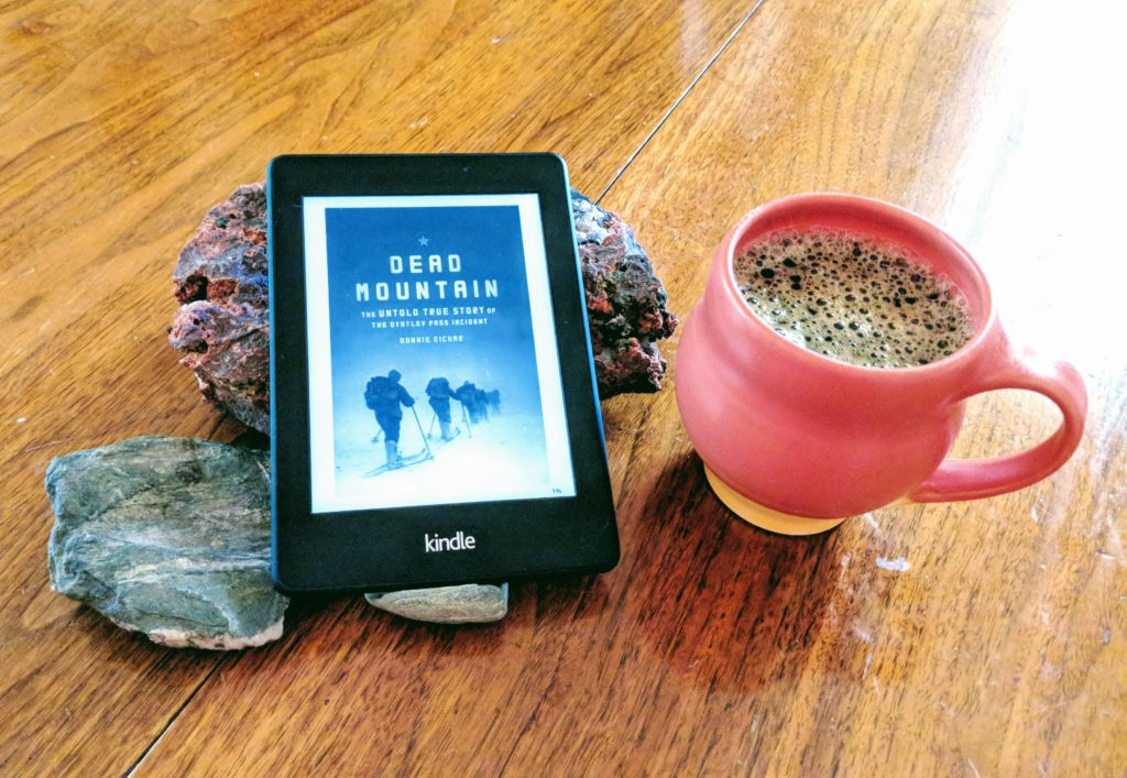 My Kindle Paperwhite propped up on some rocks on my dining room table, with a mug of coffee nearby.