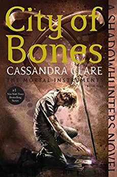 The cover of City Of Bones features a scruffy looking dude knelt before some kind of magic book, with a staff in his hand.
