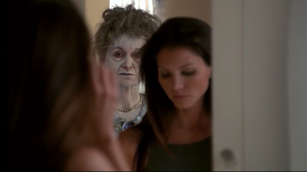 Cordelia is oblivious in front of her mirror as a ghostly lady (probably in her sixties) is reflected behind her.