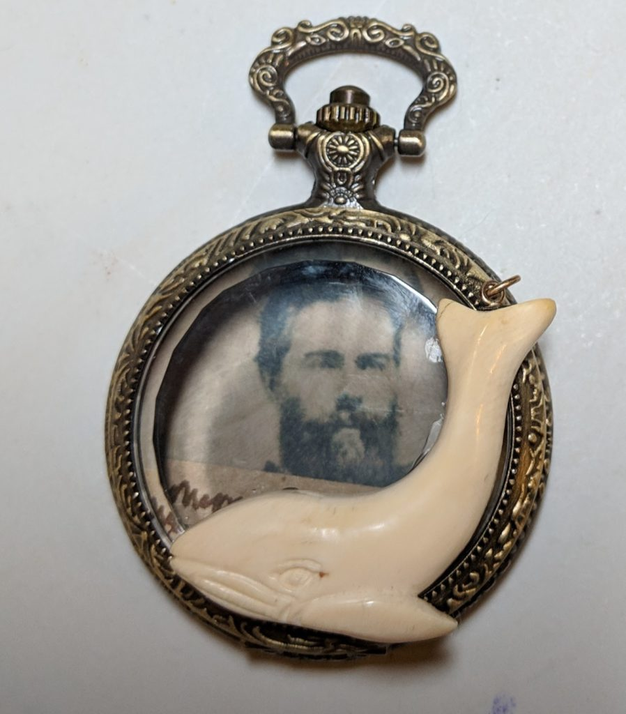 A pocket watch with a glass lid. Inside is a photo of Herman Melville. An ivory whale charm is affixed to the front edge of the glass.