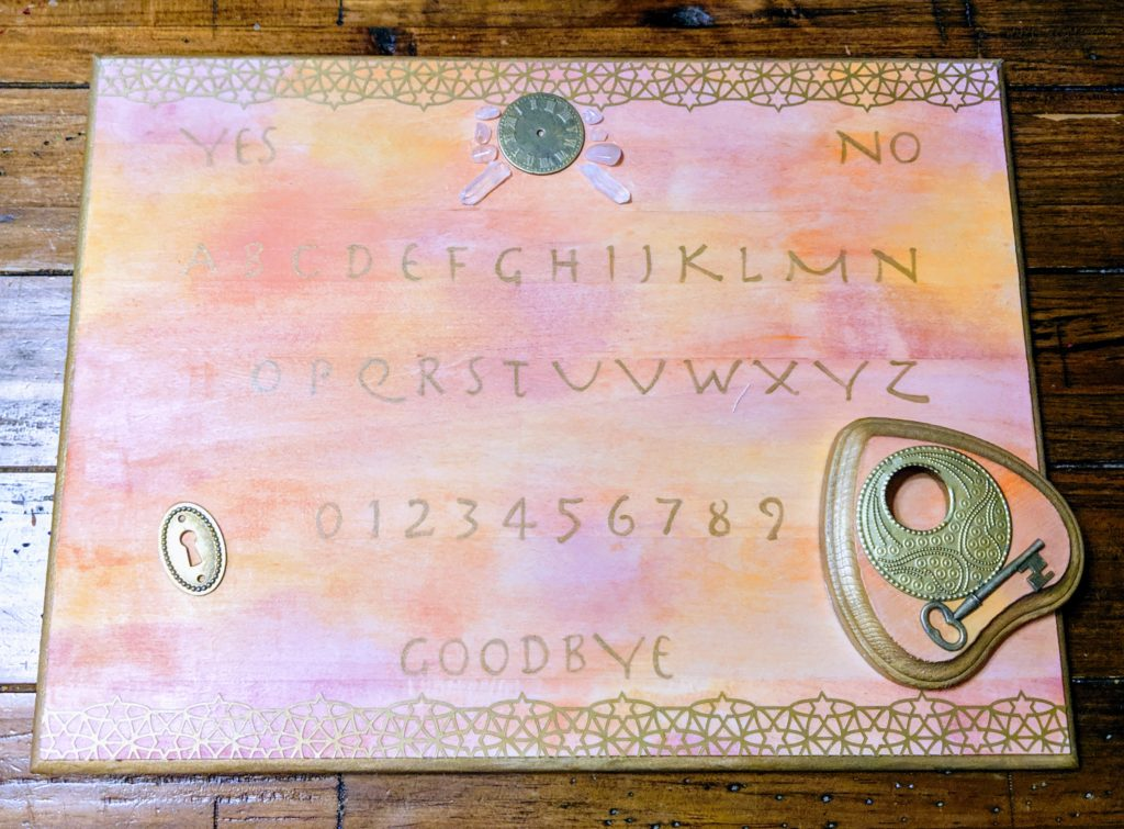 I made a ouija board. It's watercolor stained with pink and orange and brown and has gold lettering and embellishments like a keyhole and a watch face and various crystals.