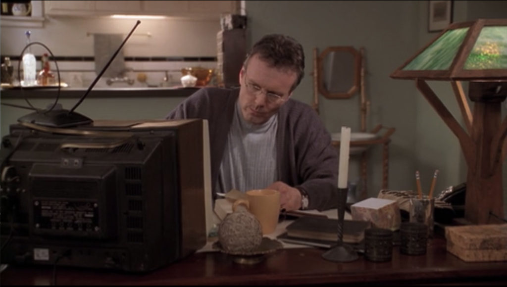 Giles is at his desk, upon which there is now a television in addition to his mystical stuff. He's kind of reading an old book while he's eating and having a big mug of tea. He's wearing two sweaters and neither particularly go with each other or particularly fit well.