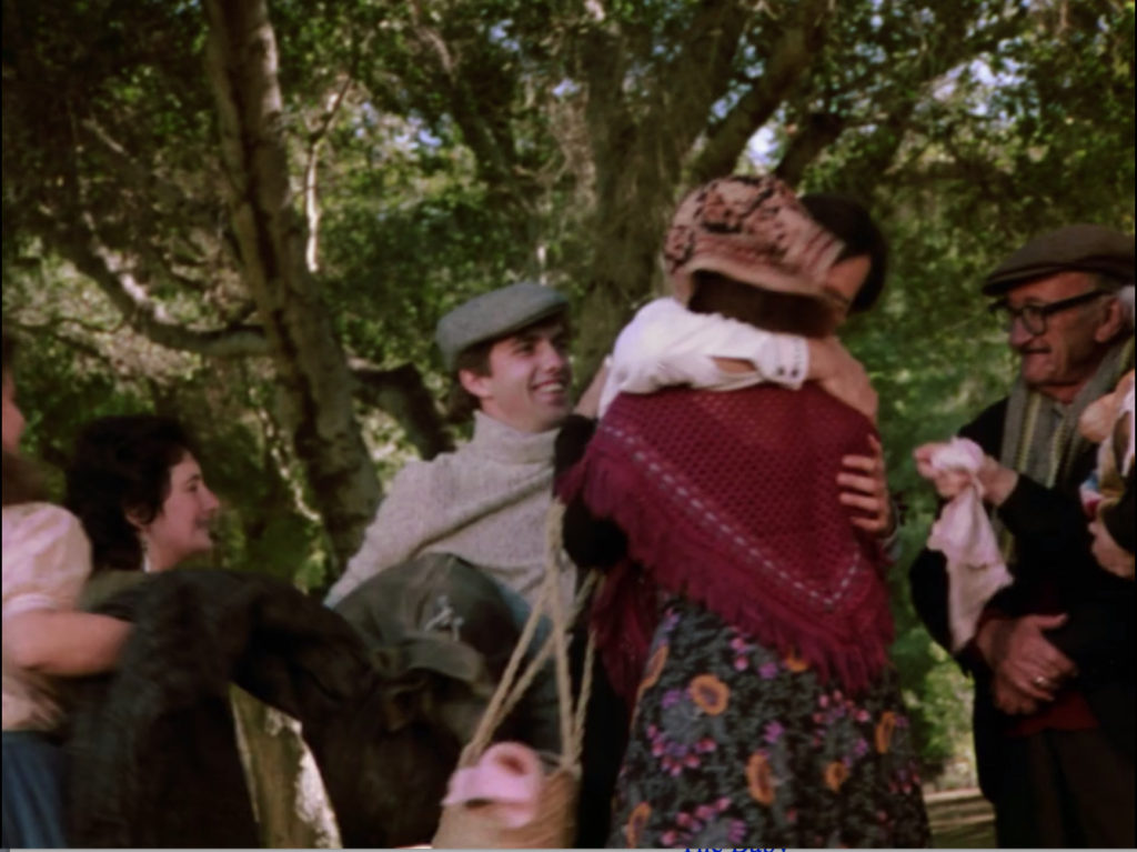 Balki is hugged by a woman in a kerchief, red shawl, and floral print skirt. A girl in a peasant blouse stands to the left of the shot, with another woman. A young man in a turtle-neck sweater and jaunty cap are behind them. An old man with glasses, a newsboy cap, and a scarf stands to the right