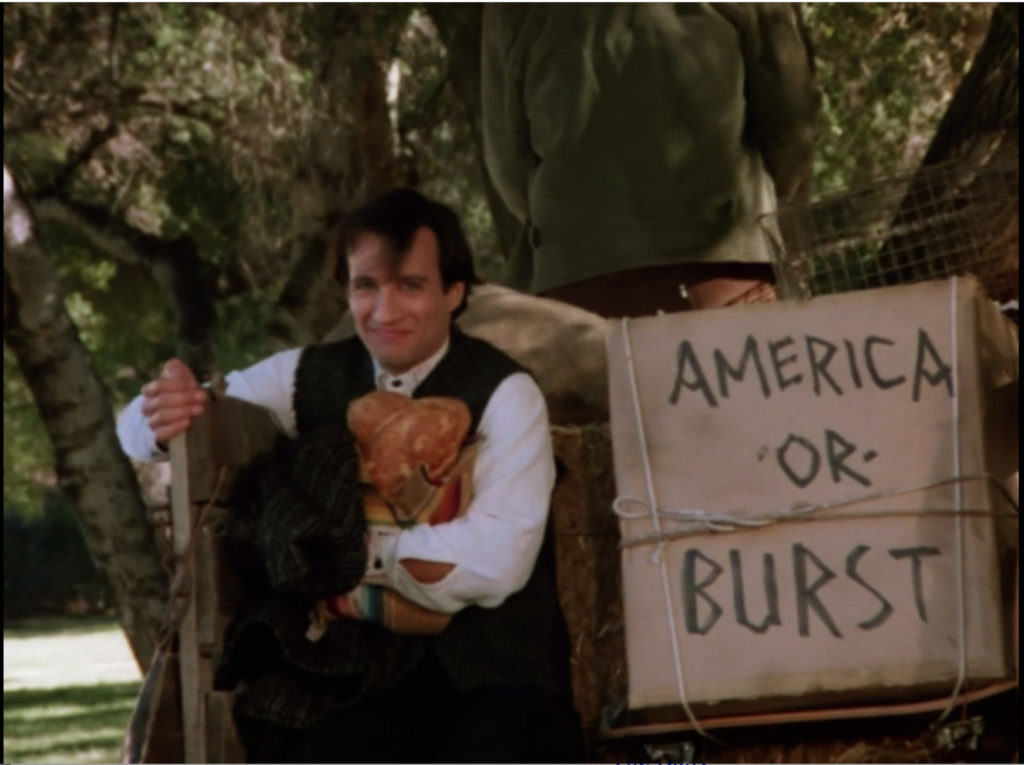 "Balki is riding on the back of a horse-drawn cart. The cart is filled with straw, a caged chicken, and an ""America or Burst"" sign."