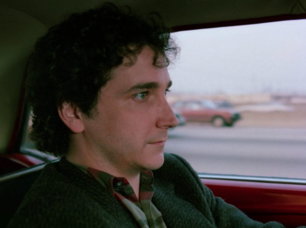 Larry is driving and looking incredibly tense. Like, to the point that I'm working if they actually made him drive on the Chicago expressway while someone filmed him from the passenger seat.