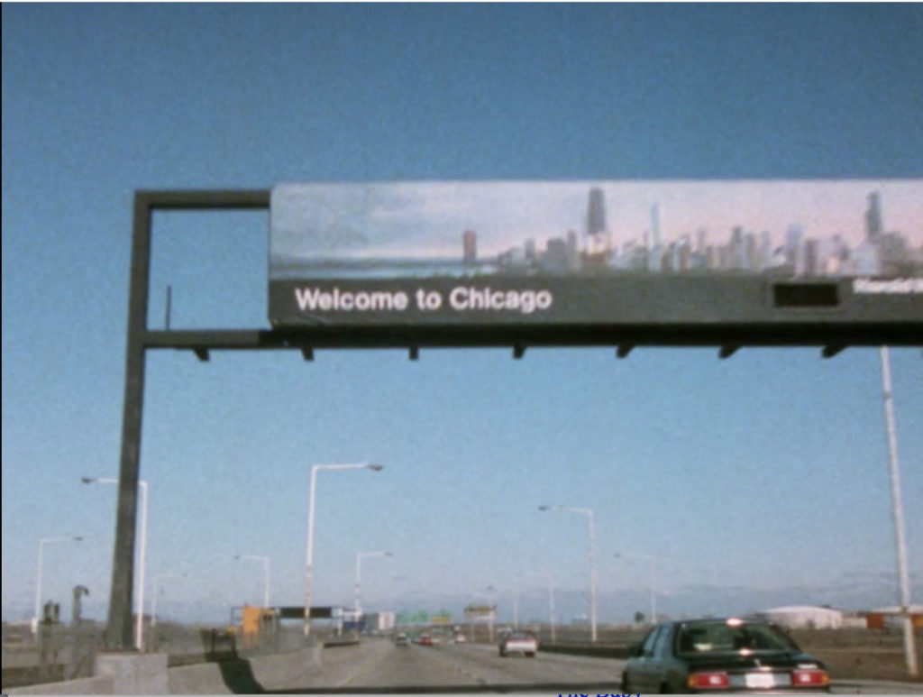 "A shot of the highway with a ""Welcome to Chicago"" sign over it."
