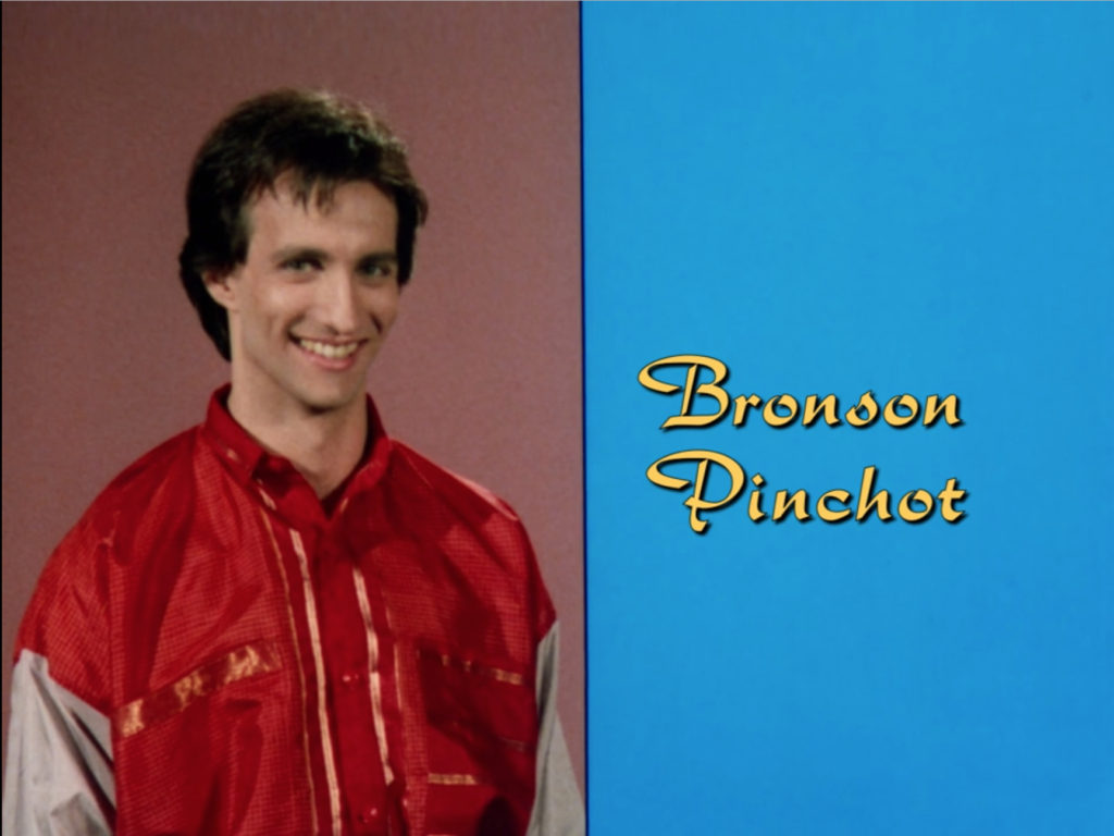 Bronson Pinchot, still in that '80s windbreaker, on a vertically split screen with his name in that same hideous yellow font but on a field of intense blue that clashes with every other color on screen.