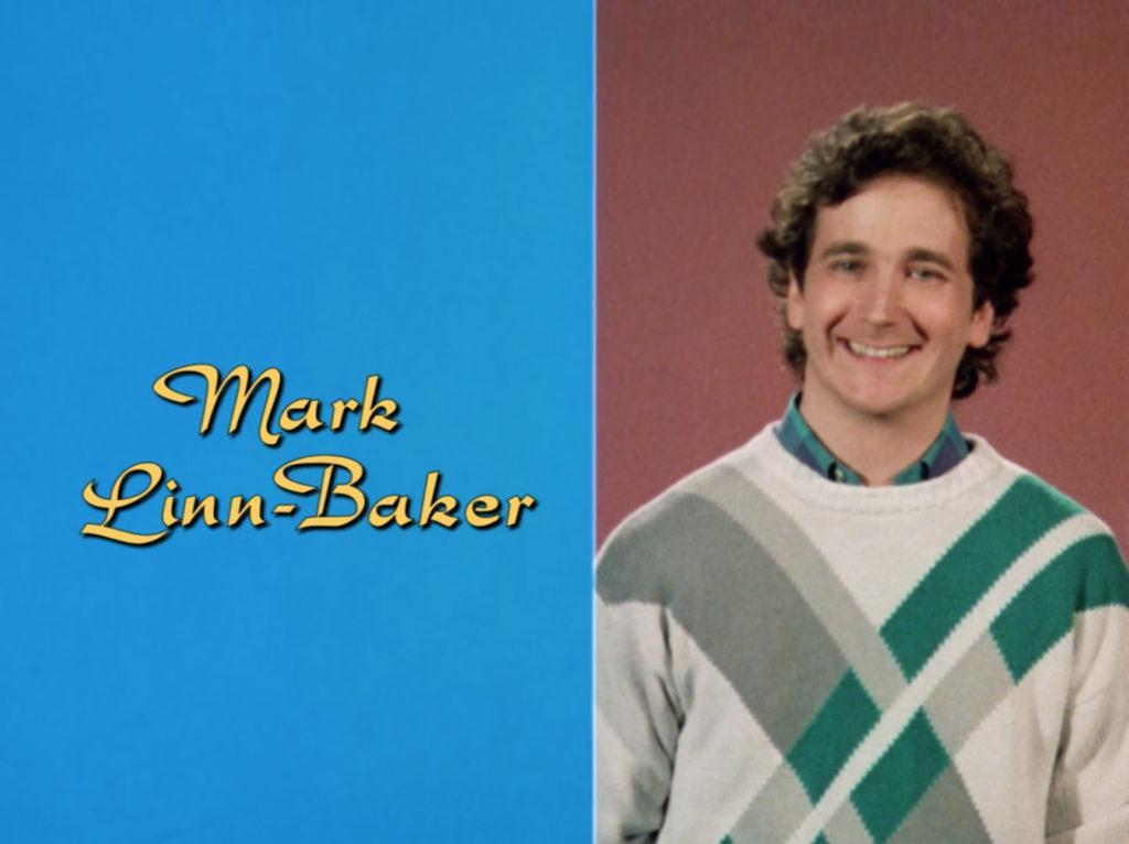 Mark Linn-Baker in the same type of set up, but instead of his original sweater, he's in a way more '80s one with diagonal, intersecting slashes of green and gray.