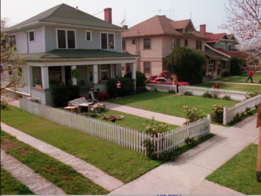 A gray house at the end of a row of houses, all two-story with small front lawns and white picket fences. The gray house has what appears to be a full living room set on the damn lawn.