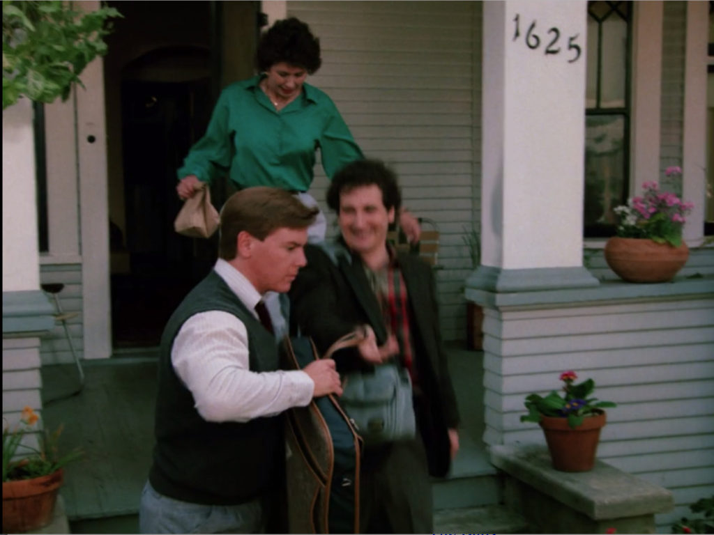 A slightly motion-blurred shot of Linn-Baker's character, Larry, heading down the porch steps of the gray hous. He's got a camera bag over his shoulder and is followed by a woman who is clearly meant to be his mother, as she carries a sack lunch. Another adult man, this one in a sweater vest and button down like he's wandered in from a movie about young Wall Street hustlers hands Larry a garment bag.