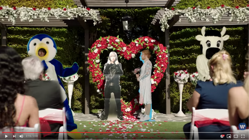Where to begin. Okay, the overall scene is a wedding. Ed Sheeran in a penguin suit dances on one side of the screen, while the cow mascot dances on the right. In the middle, Ed Sheeran in a wedding dress stands under a heart-shaped arch of roses, marrying a Justin Bieber cut-out.