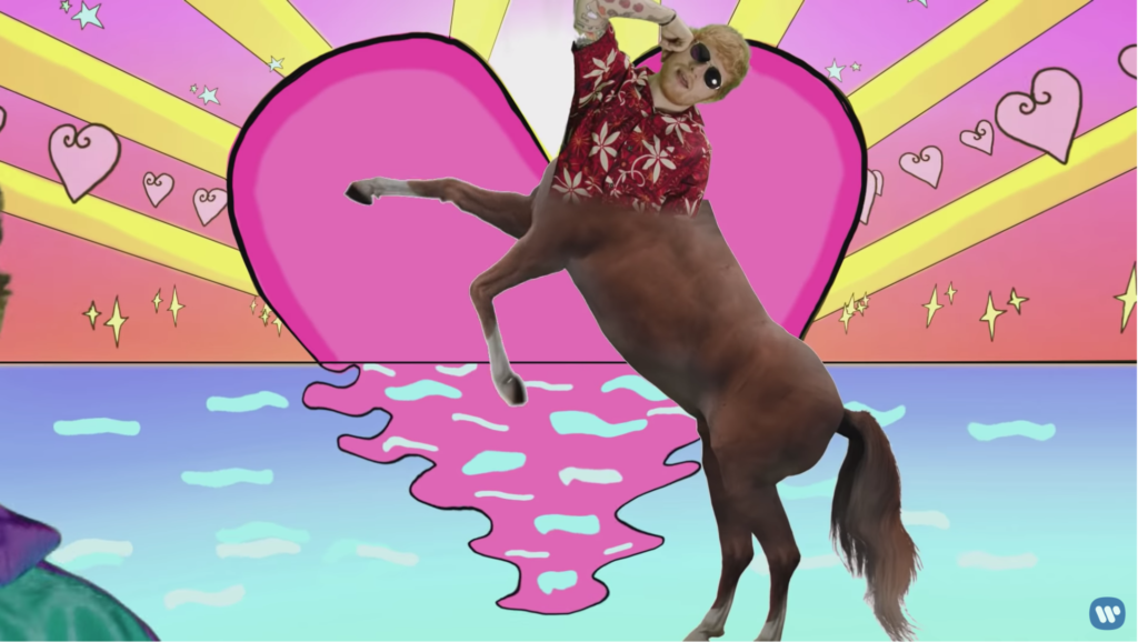 The top half of poolside Ed is green screened over the body of a rearing horse, in front of a giant pink heart setting like the sun into neon blue water.
