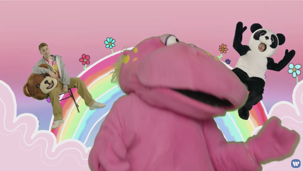 Justin, in totally normal street clothes, is sitting in a folding chair on an animated rainbow while holding the bear suit head in his lap. Miserable Panda Ed is on the other side of the rainbow. The pink hippo dances in the foreground