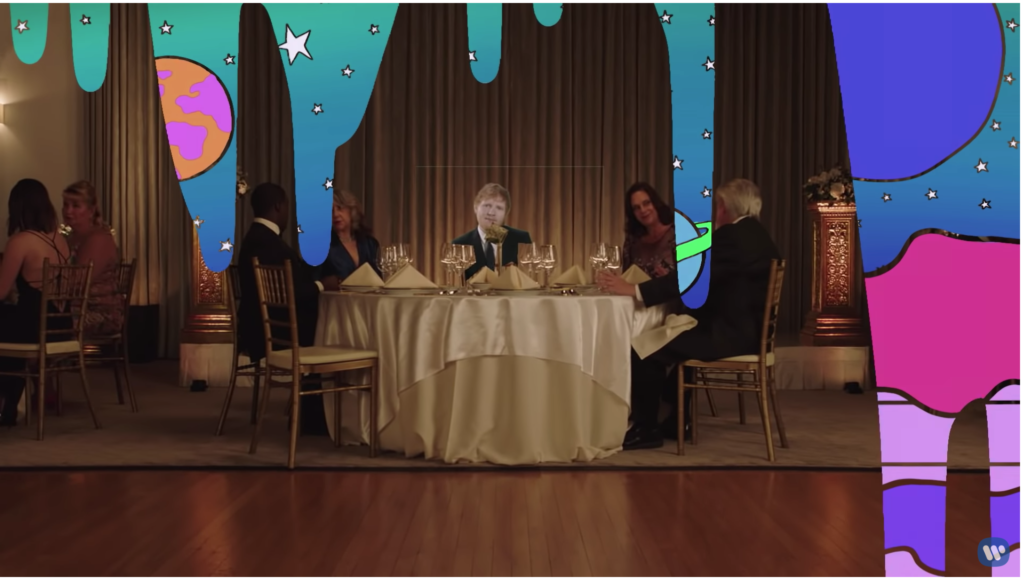 Ed, still horribly green screened, is sitting at a table in the fancy restaurant, but now there are drips of a second background cascading down, revealing brightly colored planets and stars that look like a kid drew them in art class.