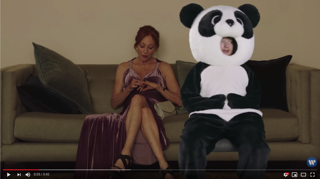 Ed is wearing a giant Panda mascot suit. His face is visible through a hole where the panda's mouth would go. He's badly green-screened onto a couch beside a beautiful, disinterested woman.