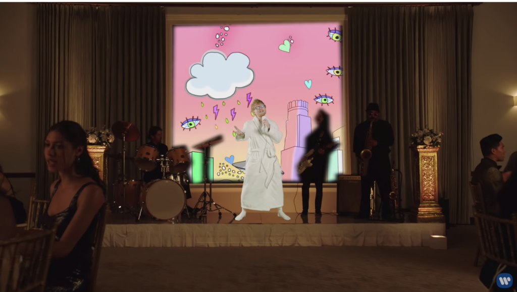 Ed is on a stage singing in a bathrobe and white socks, in front of a backdrop of a pink sky with falling clouds, hearts, and eyes.