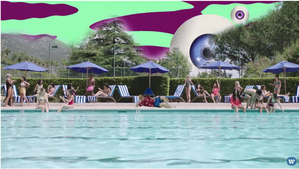 Ed is green-screen lounging pool-side in the damn socks, shorts a dad would wear, and a flowered button-down shirt. The sky is purple and green and there is a giant, floating CGI eyeball.