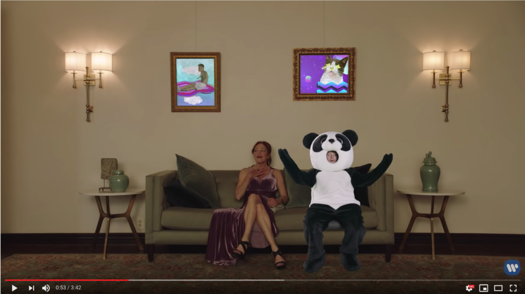 Back on the couch with the disinterested woman, Ed is still in his panda suit. Now, though, we see two framed pictures above him, one of a cat surrounded by very 1990s graphics and the other of Justin Bieber in an inflatable rowing raft.