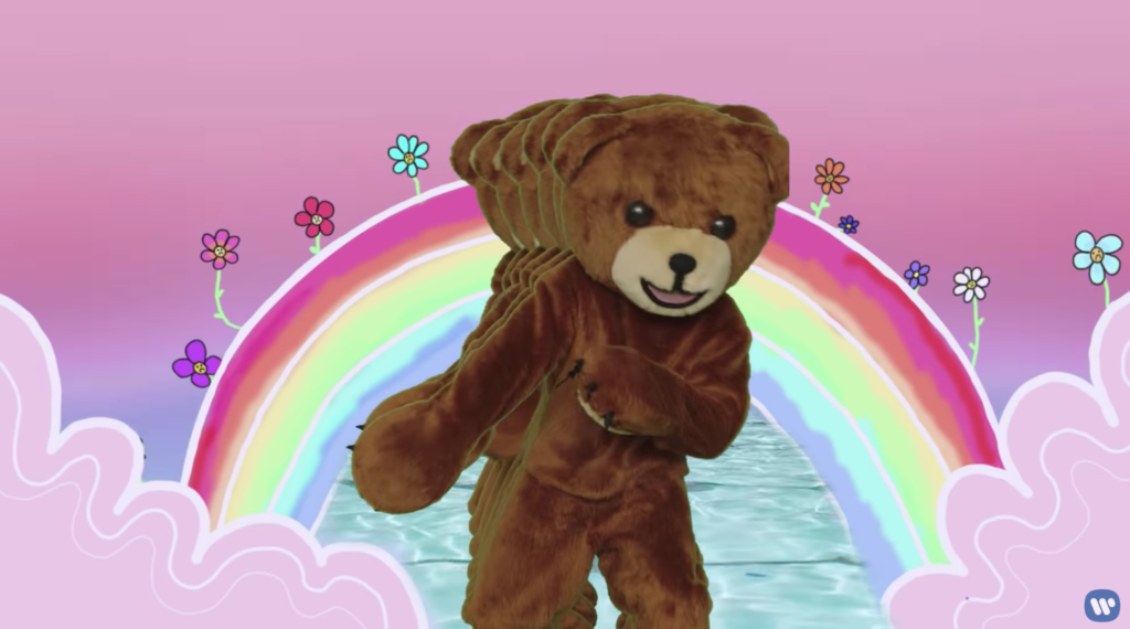 Someone in a Teddy Bear suit dancing in front of a rainbow. There is a weird trailing effect of more bears behind him as he dances.