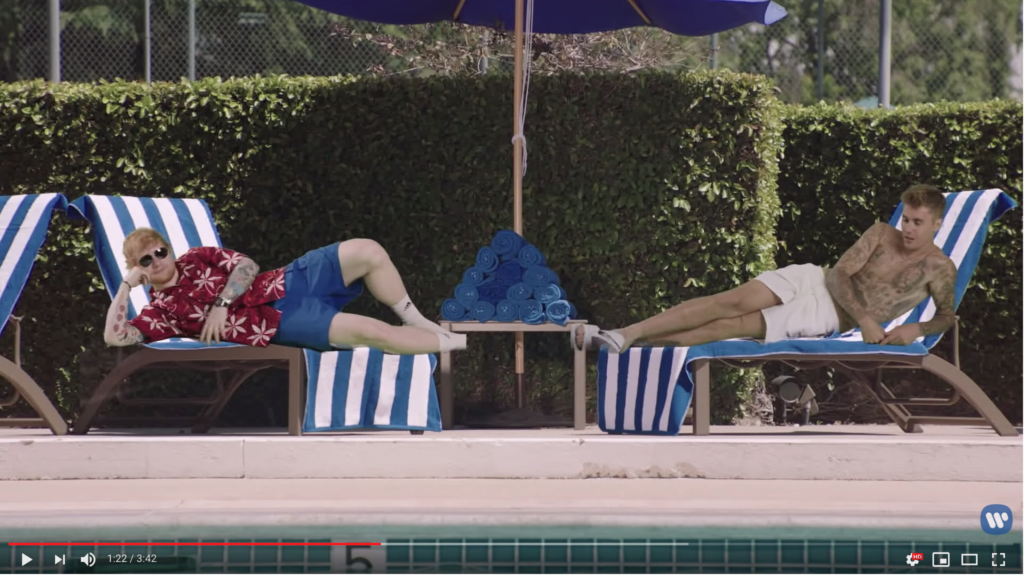 Ed in his pool clothes and Justin shirtless in white shorts are green screened onto poolside lounge chairs.