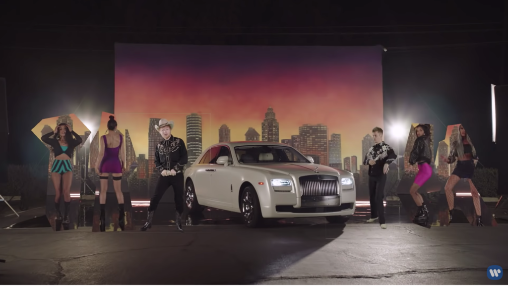 Ed and Justin are both dressed by cowboys. They flank a white Bentley. There are sexy video girls dancing on either side of them, and there is a painted backdrop of a city skyline at sunset.